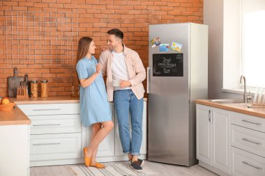 Happy couple near refrigerator in kitchen