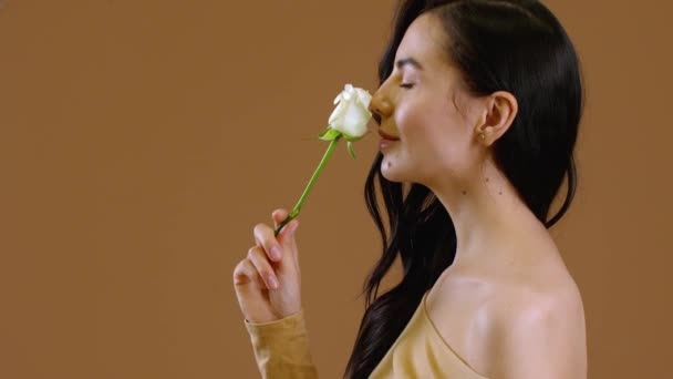 Beautiful young woman with white rose on color background
