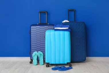 Packed luggage near color wall. Travel concept