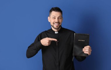 Handsome priest with Bible on color background