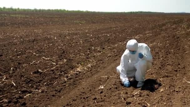 Vědec studující vzorek půdy v terénu