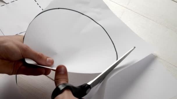Man cutting paper sheet with drawn circle, closeup