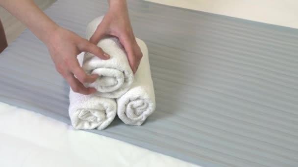 Pokojská dávat čisté ručníky na postel v hotelovém pokoji, detailní záběr