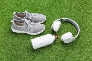 Sportive shoes, bottle of water and headphones on color background