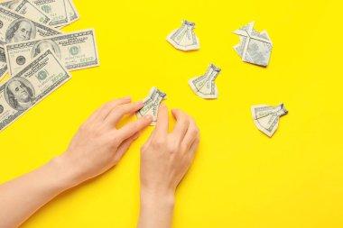 Renkli arka planda dolar banknotlarından origami figürleri yapan kadın