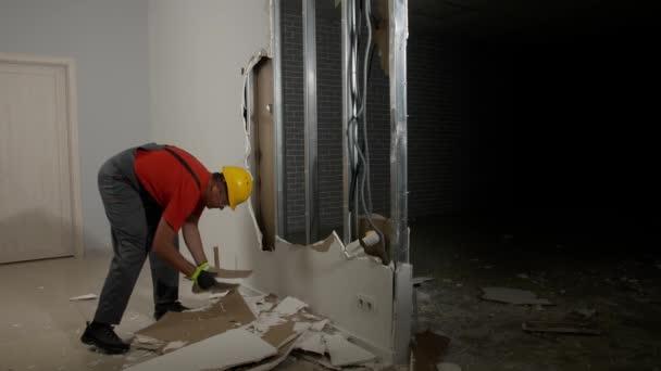 Männlicher Bauarbeiter durchbricht Wand aus Gipskartonplatten im Haus