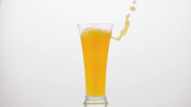 Eiswürfel fällt in Orangensaft
