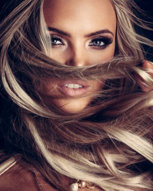 blond lady with beautiful hair on grey
