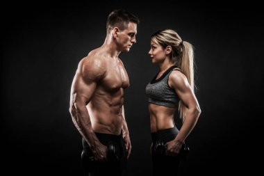 Sporty young couple posing on black background