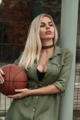 Beautiful blonde in green dress with big boobs with choker around her neck is standing on basketball court with basketball