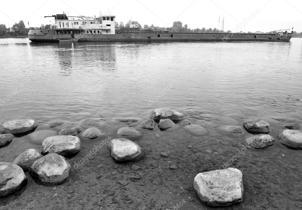 Cargo ship on the Neva river, outskirts of St.Petersburg at cloud summer day. Black and white.