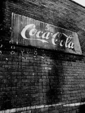 Vintage Coke Cola sign hanging on a wall outside a restaurant in downtown Gilbert Arizona which is located in the Southwest part of the United States. This sign shows Coke Cola selling for five cents.