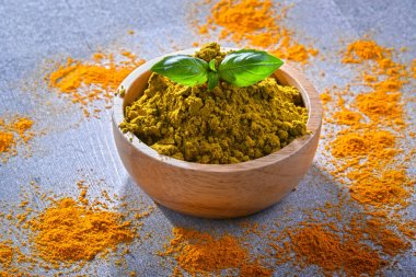 Composition with bowl of curry powder.