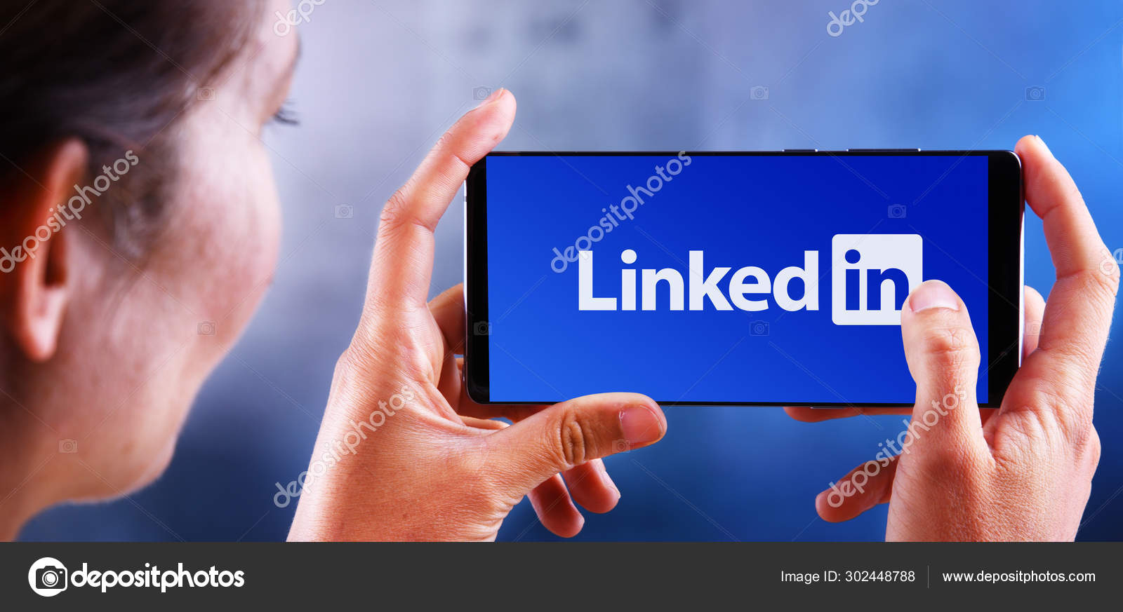 Woman Holding Smartphone Displaying Logo Of Linkedin Stock