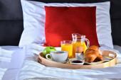 Frühstück auf Tablett im Bett im Hotelzimmer.