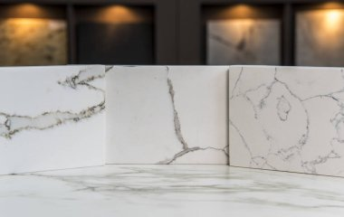 Marble kitchen counter top color samples of White Carrara inside showroom with more samples in blurry background
