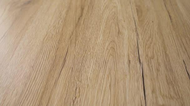 Vrcholové posouvání 4k pomalý videozáznam moderního tvrdého dřeva. Hotové patro je vyrobené z přírodního Rudého javorového dřeva s hnědou zrnka a čiré tvrdé dřevěné barvy. Koncepce renovace a zlepšení domova