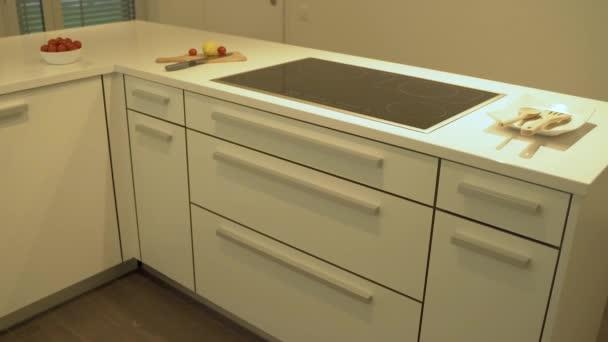 Design moderní bílé kuchyně v bílých plochých skříňkách s křemenným pultem v pomalém mo. Jako dekorační design kuchyně je v kuchyni zahrnut i jídlo a platky.