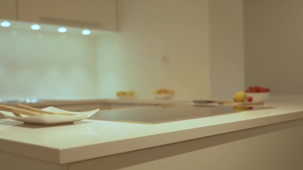 Krásný pomalý pohyb moderní kuchyňské skříňky, bílá kuchyňská zátop, elektrická kuchyně a dřez. Jako dekorační design kuchyně je v kuchyni zahrnut i jídlo a platky.
