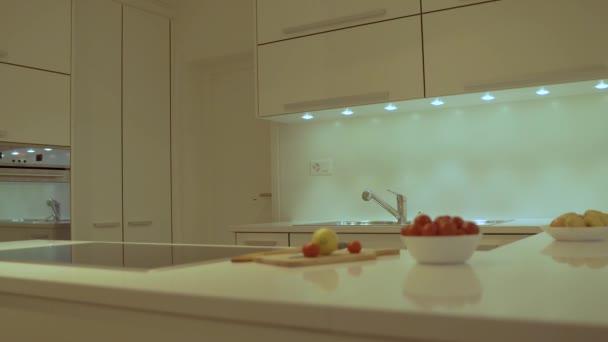 A modern stílus konyha design lapos fehér szekrény, fehér konyhai pult tetején készült kvarc elektromos főzőlap, tartomány és mosogató. Díszítőelemek és tányérok szerepelnek, mint a konyha tervezési koncepció.