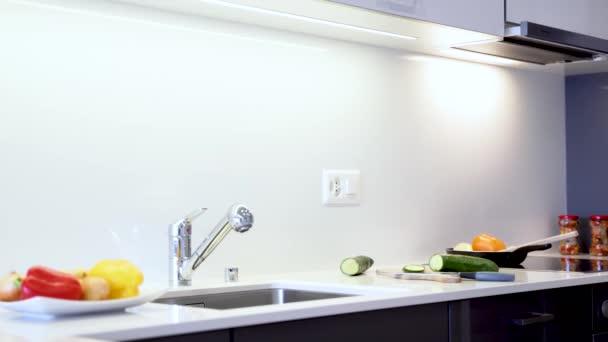 Krycí deska moderní křemenné desky. Kuchyňský pult se skládá z bílé barvy s chromovanými dřezem a kohoutkem. Kuchyňské skříňky jsou vyrobeny z moderních černých plochých panelů.