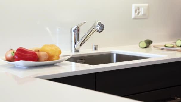 Kuchyňská deska z žulové desky. Je vyroben z moderní bílé barvy s chromovým dřezem a kohoutem. Kuchyňské skříňky jsou vyrobeny z černých plochých panelů.