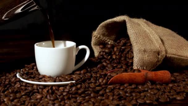 Nalití čerstvé kávy v bílém šálku kávy s fazolemi kolem