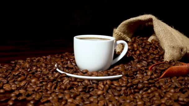 Fresh coffee inside white coffee cup and coffee beans