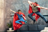 father and son in superhero capes and masks jumping on sofa at home