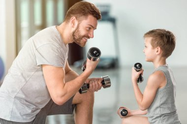 little kid training with dumbbells together with father at fitness center
