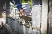 Fotografie Arbeiter mit Beton Zement Mörtel blockwand auf Baustelle
