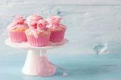 Torte della tazza rosa su sfondo blu