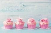 Fotografia Torte della tazza rosa su sfondo blu