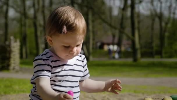 Aranyos kis baba lány játszik ő ül egy homokozó, játszótér, játékok