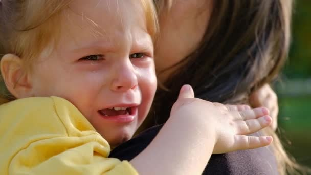 Close-up portrait of a cute crying little girl sitting in her mother arms