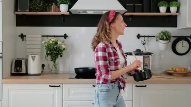 Unbekümmert fröhliche junge Hausfrau tanzt allein beim Kochen von Mahlzeiten