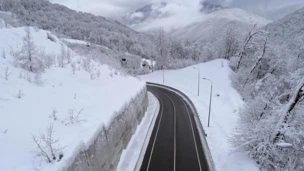 Letecký pohled na klikaté cestě horská lanovka gondola zvedání. Zastřeleni během sněžení. Zakřivené nadjezdu silnice. Zimní zasněžené krajiny. Mraky nad horami