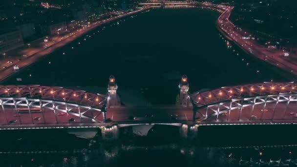 aerial view. Flight over the bridge during the ice drift. Night shot. Head over parallax crane shot. Medium traffic on bridge. Amazing bridge retro constructions.