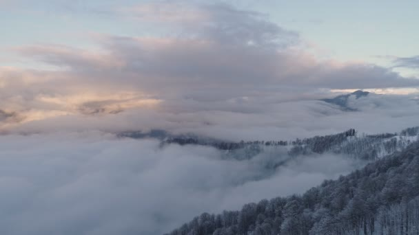 Aerial long flat flight over clouds in winter mountains. 4K video from drone. Drone move forward over clouds in mountains during sunset. bewitching view above clouds