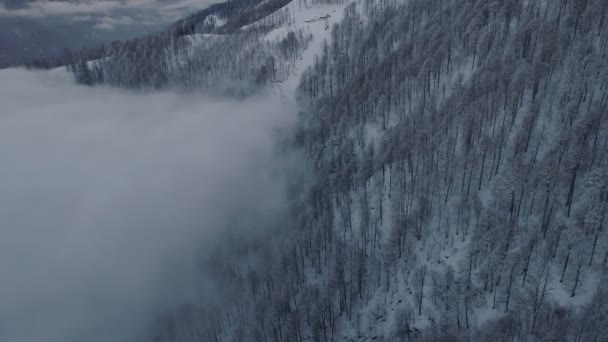 Drone fly above clouds in mountains. Cable cars in Snow covered forest. Amazing winter snow view. Aerial view, drone fly right and camera move up.