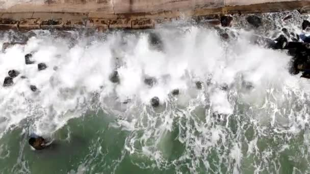 Aerial top view storm in sea, waves crashing on wave breakers