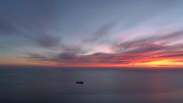 Letecký výhled létá přes moře s osamělou lodí na obzoru během úžasné sluneční záse.