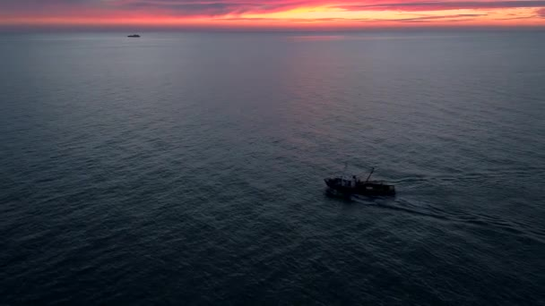 Aerial view fishing boat in sea with beautiful sunset red sky on background