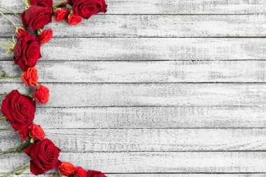 Top view of red roses on grungy grey wooden table with copy space