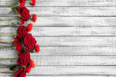Top view of beautiful red roses on grungy grey wooden table with copy space