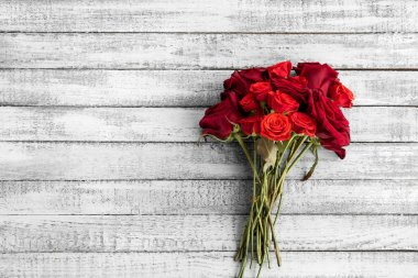 Top view of beautiful red roses bouquet on grungy grey wooden table with copy space