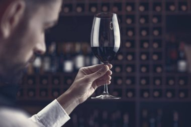 close-up shot of young sommelier tasting red wine in cellar