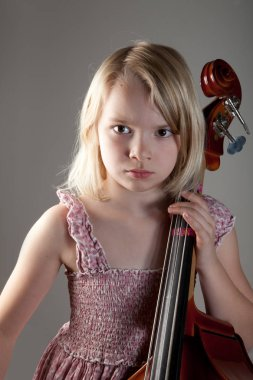 Portrait of a young girl in studio with cello