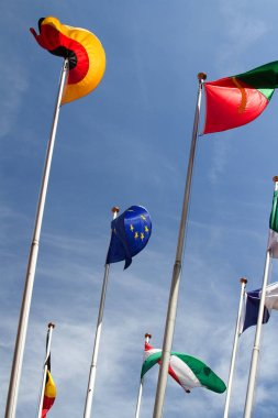 Many european flags in the wind against the blue sky, low angle view