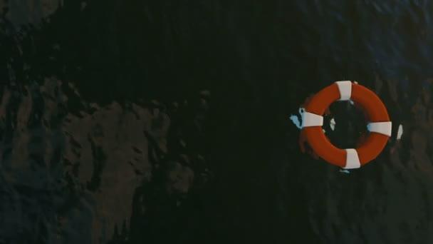 Rettungsring schwimmend auf Meer und Haie schwimmen unter, verkleinern Sie die Ansicht